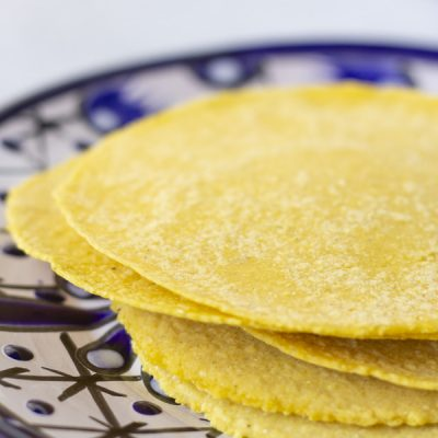 Blue plate with yellow tortillas stacked on top.