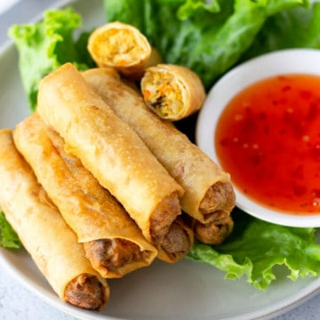 Fried Spring rolls stacked on a plate of lettuce and a side of sweet chili dipping sauce.