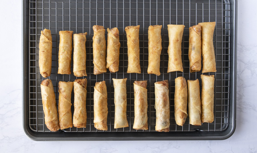 Cooked spring rolls cooling off on a wire baking rack.