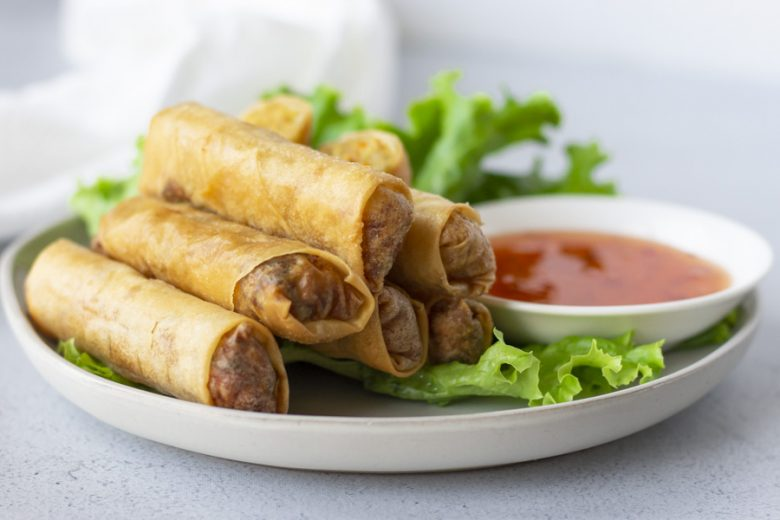 Crispy rolls on a bed of lettuce on a plate with a side of sweet chili dipping sauce.