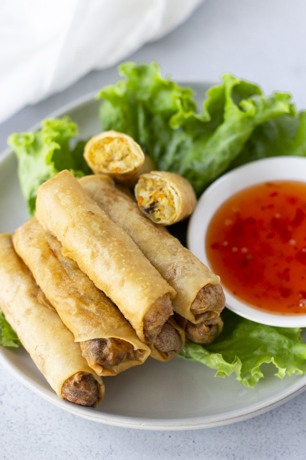 Spring Rolls on top of a bed of lettuce on a plate with a side of sweet chili dipping sauce.