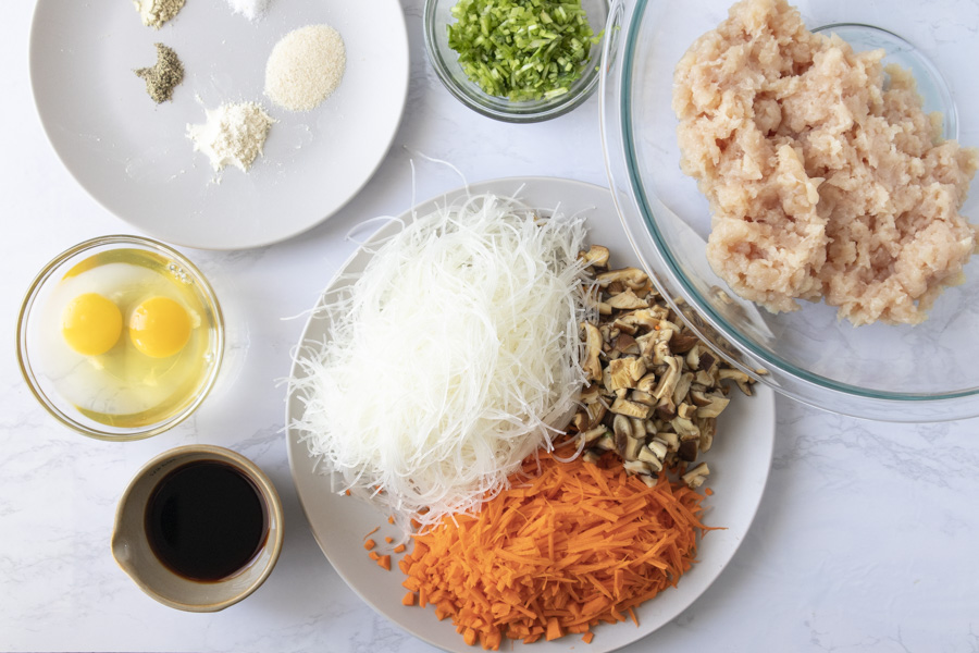 Overhead view of ingredients (ground chicken, noodles, carrots, mushrooms, cilantro, eggs, soy sauce, and spices).