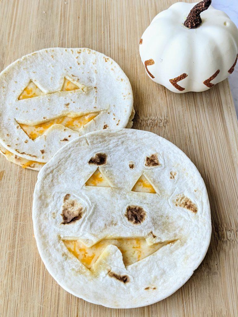 Two Quesadillas cut out like Jack o lanterns on a cutting board.