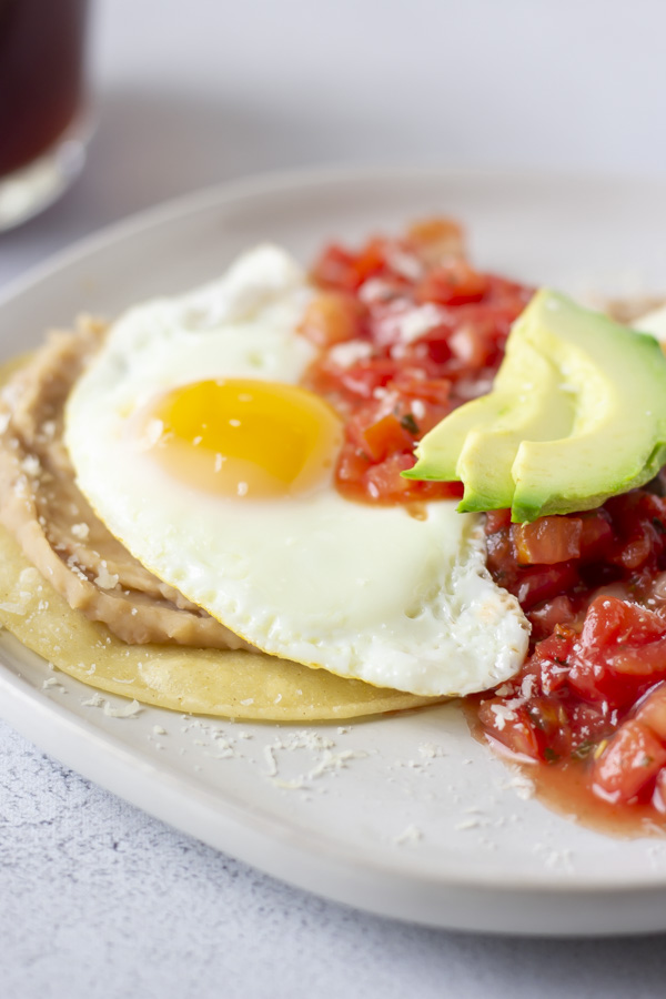 Up close view of sunny side egg on beans and corn tortilla.