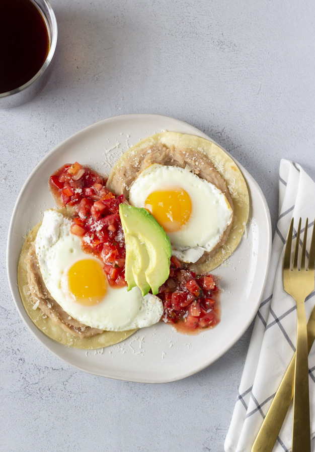Overhead view of huevos rancheros with a gold fork and knife to the side and a black cup of coffee.