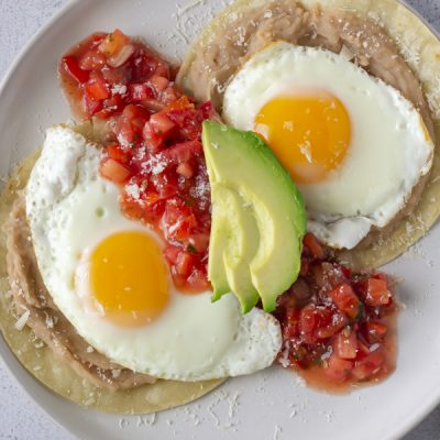 Overhead view of Huevos Rancheros on a white plate and topped with red tomato salsa and avocado
