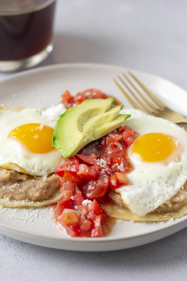 Up close view of dish with salsa down the middle of the 2 eggs and topped with avocado slices.