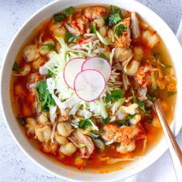 A large white bowl holding the soup and topped with shredded cabbage, cilantro, and thinly sliced radishes.