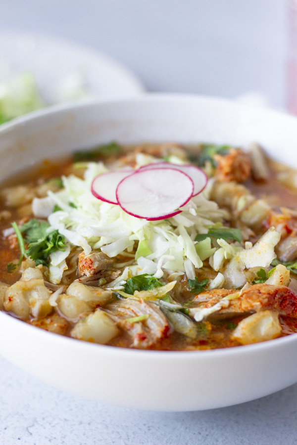 Up close view of Posole in a white bowl with shredded cabbage, cilantro, and thinly sliced radishes on top.