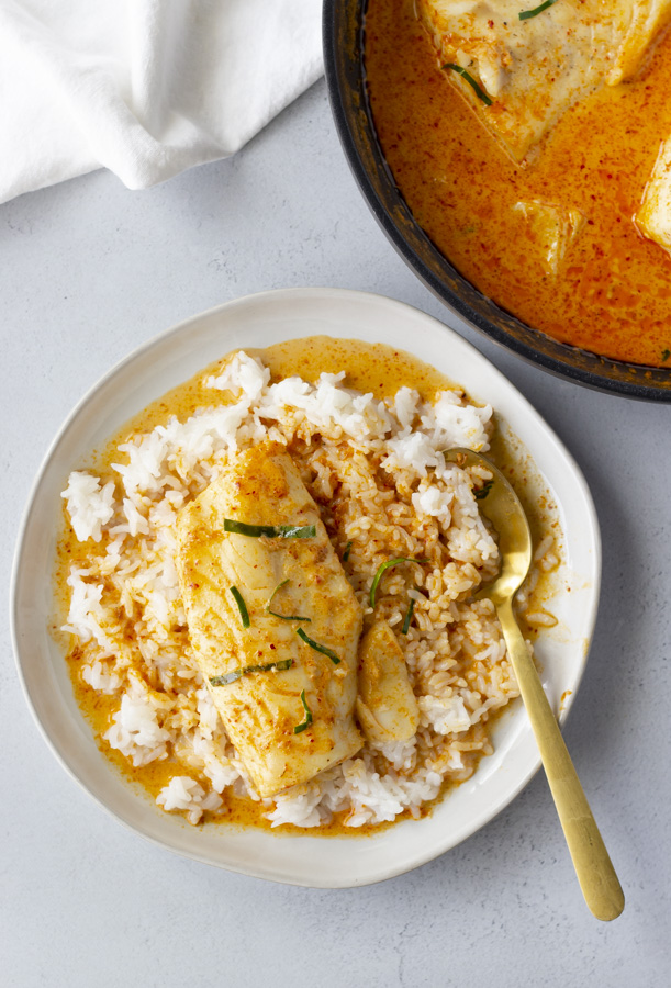 Overhead view of Red Curry Cod on a white plate and a skillet to the side with more curry.