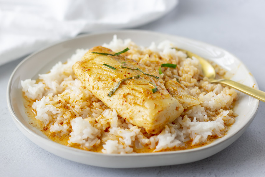 Horizontal view of rice, curry, and fish on a plate.