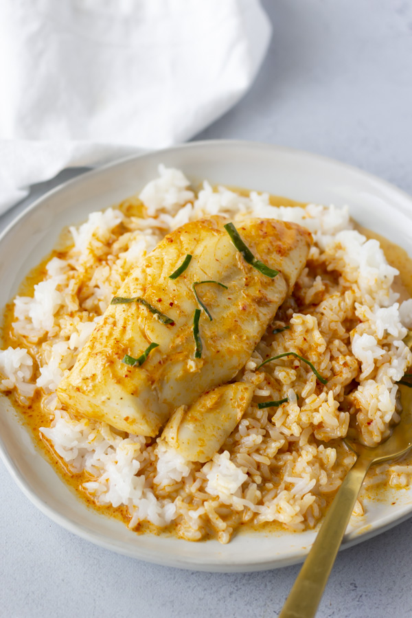 White plate with rice and red curry sauce over it and a piece of cod.