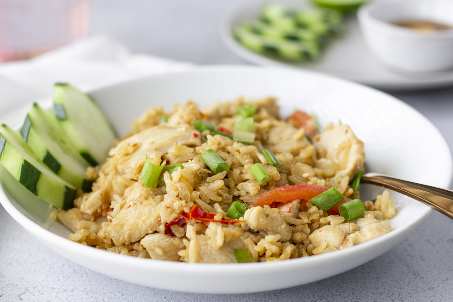Fried Rice in a white bowl with a small plate in the background with cucumber slices.