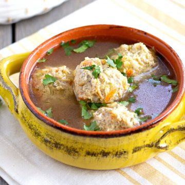 Mexican meatball soup in a yellow bowl.