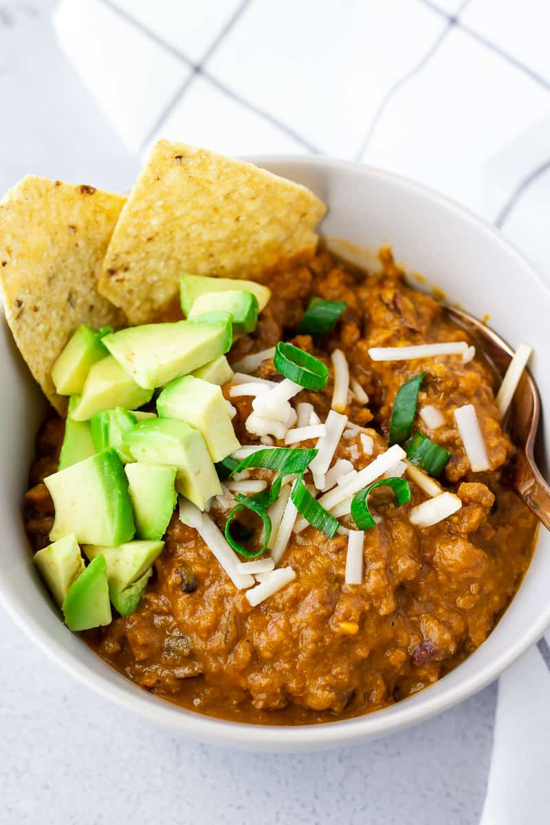Beef and Sweet Potato chili in a white bowl topped with shredded cheese, diced avocado, and tortilla chips.