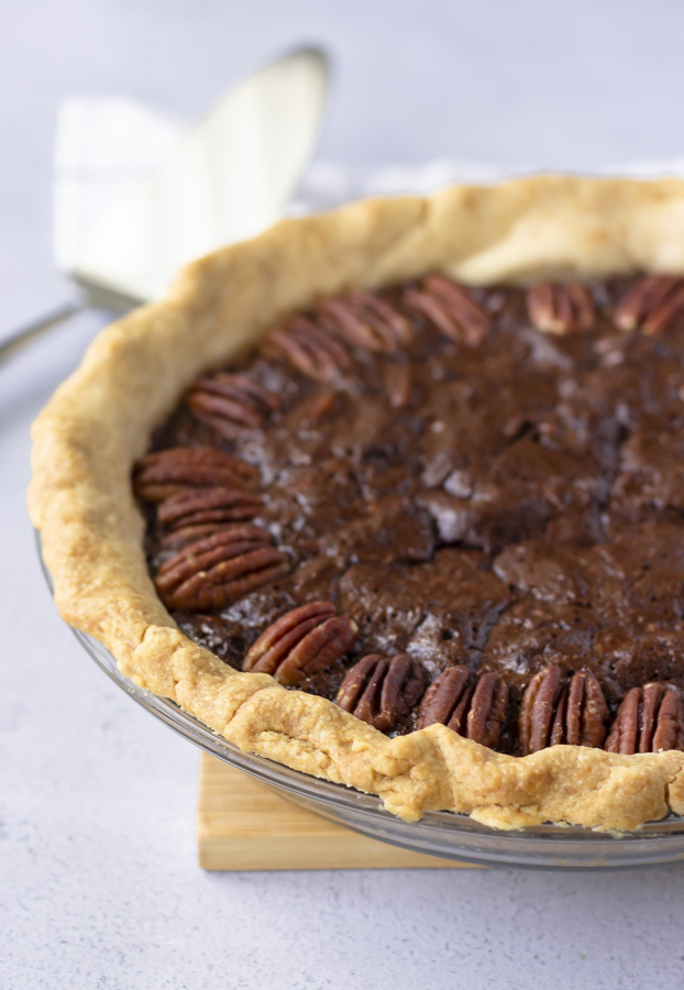 Up close view of whole chocolate pecan pie and pie server in the background.