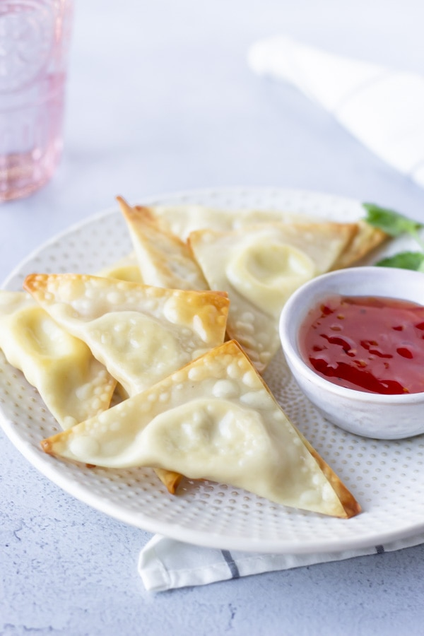 Cream cheese wontons on a plate with other wontons and a side of sweet chili sauce.