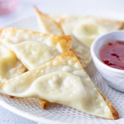 Up close view of cream cheese wonton on a plate with other wontons.