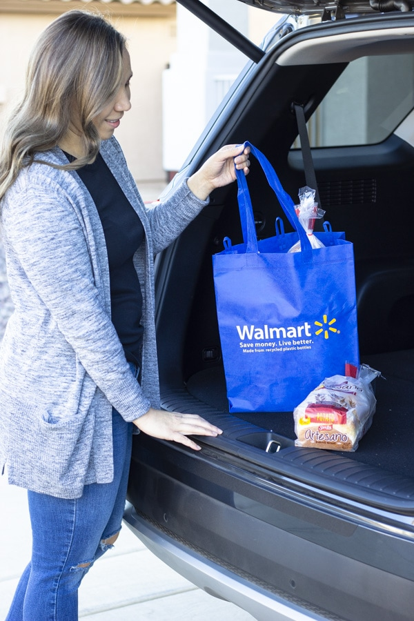 Woman at her trunk holding a blue walmart shopping bag.