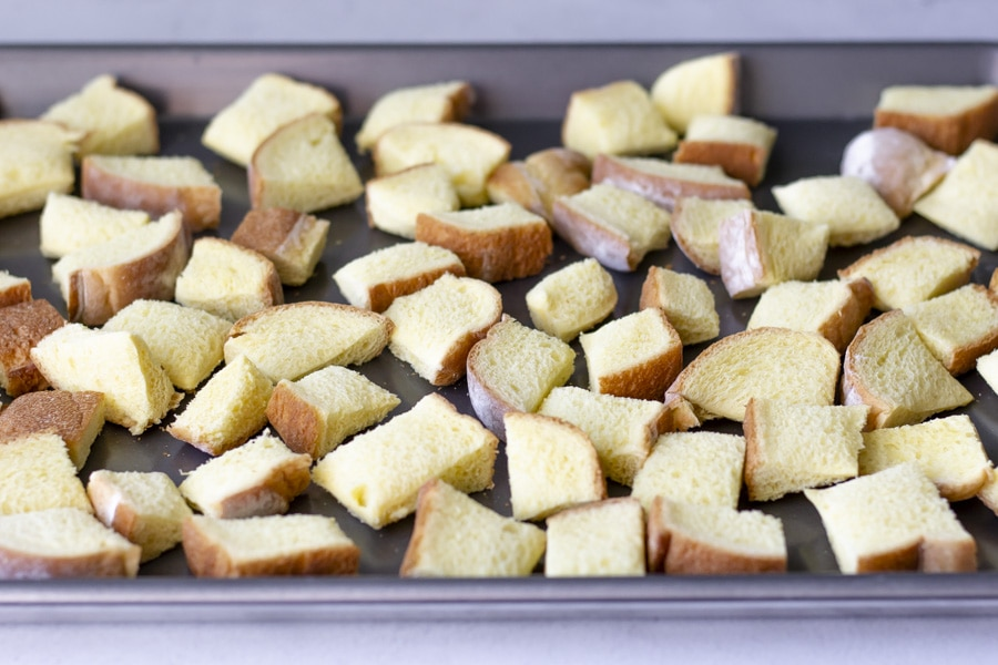 Cubed bread on a baking sheet.