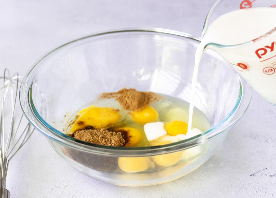 Eggs, sugar, and cinnamon in a clear glass bowl with milk being poured in.