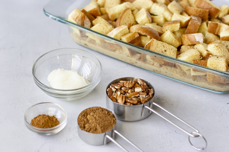 Ingredients for casserole, Bread in dish, oil, pecans, sugar, and cinnamon in individual bowls.