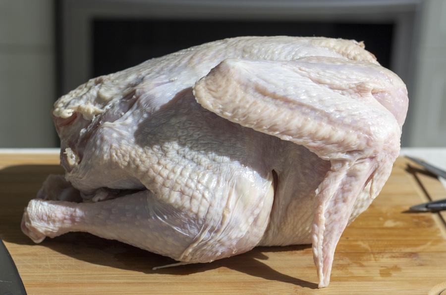 Whole raw turkey on a wood cutting board.