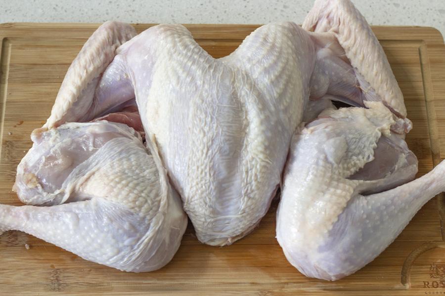 Spatchcocked raw turkey on a wood cutting board.