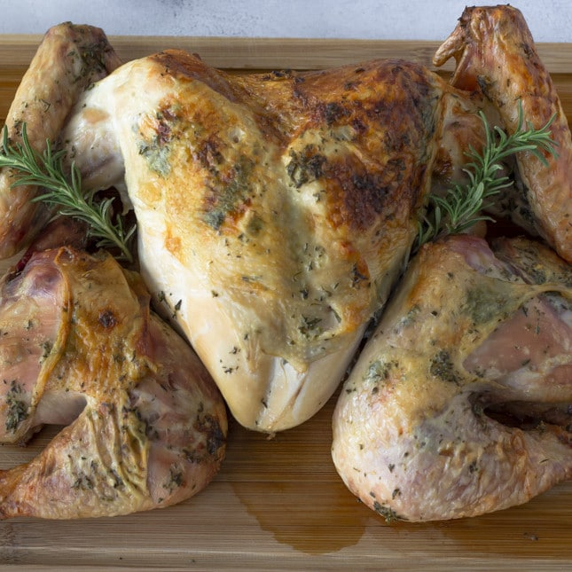Overhead view of Spactchcocked Turkey on a wood cutting board.
