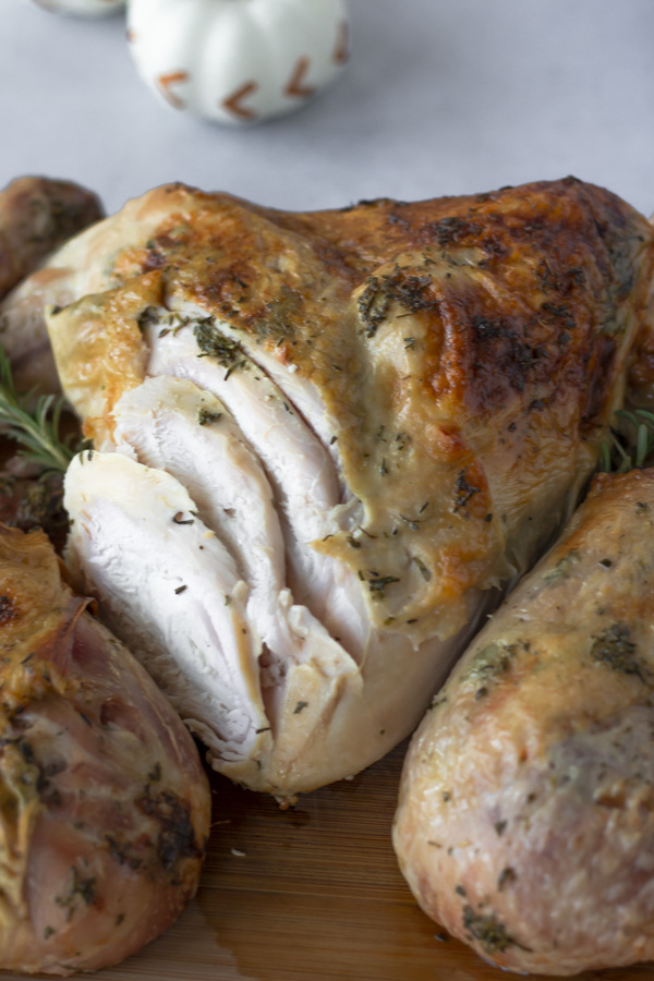 Turkey Breast sliced on one side and garnished with rosemary.
