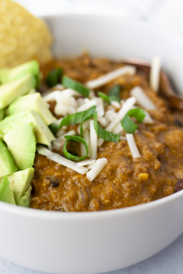 Up close view of Chili in a bowl topped with cheese, onions and diced avocado.