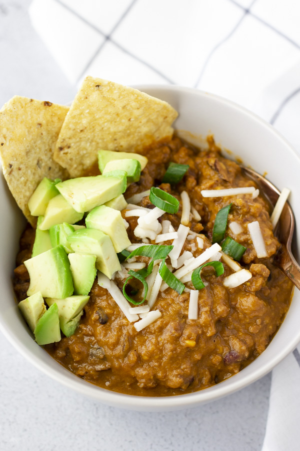 Chili in a bowl topped with cheese, onions, diced avocado, and tortilla chips.