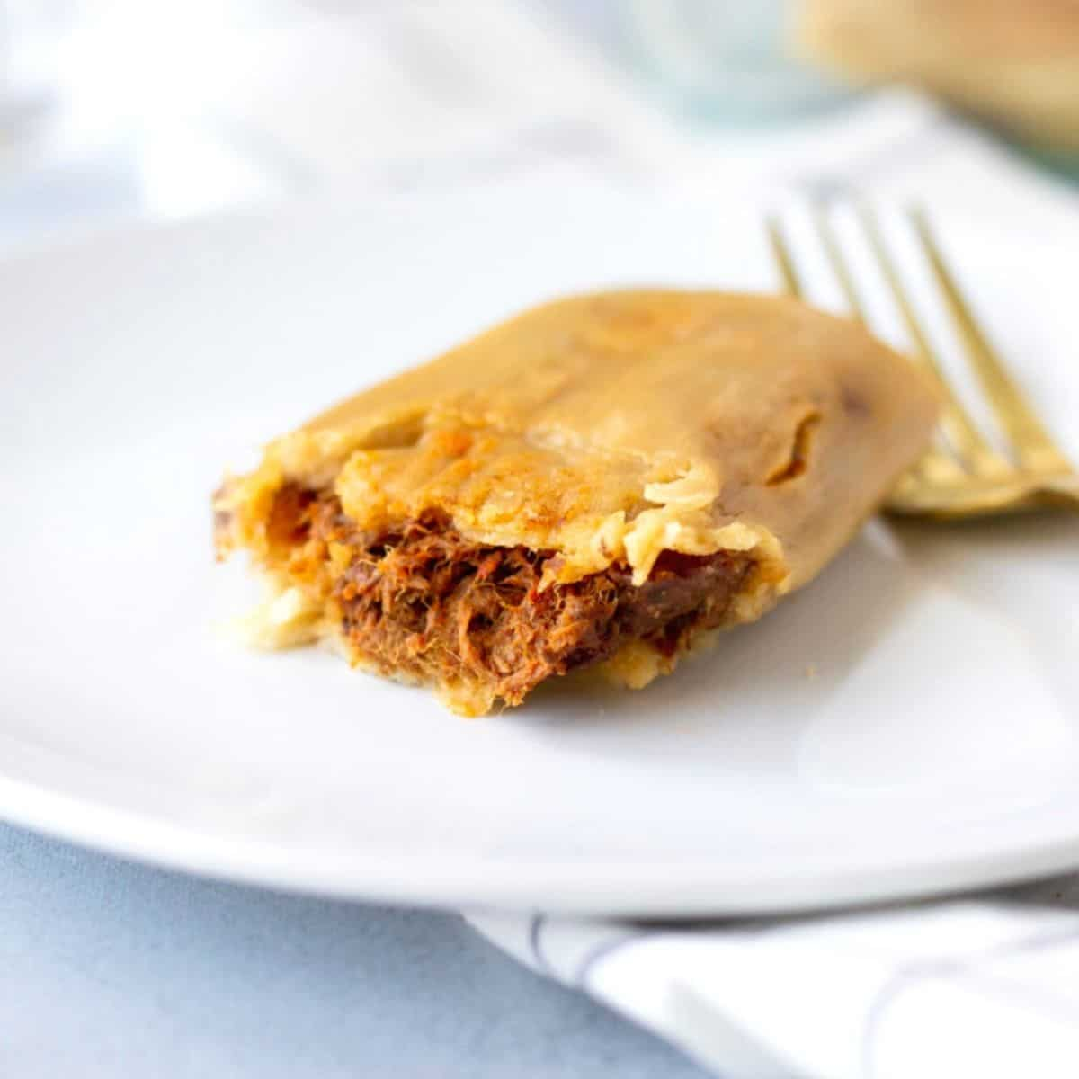 Up close view of a single beef tamale on a white plate with a gold fork on the side.