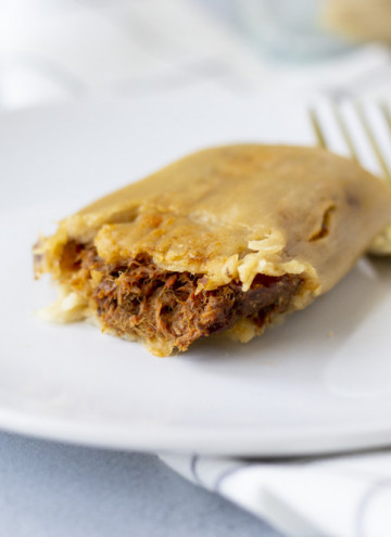 Landscape view of tamale on a white plate with a gold fork and view of been filling inside.