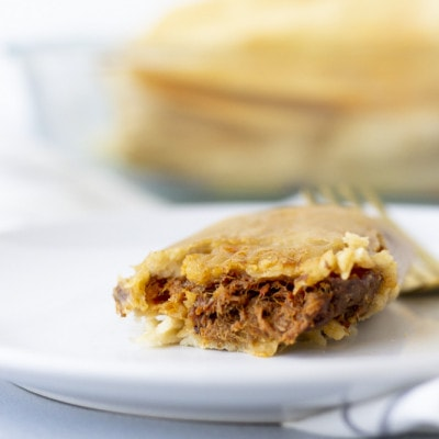 Up close view of a single tamale on a white plate and view of the beef filling.