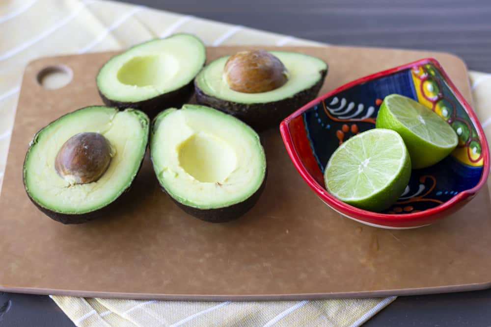2 Avocados sliced in half on a cutting board with a lime sliced in half in a small bowl.