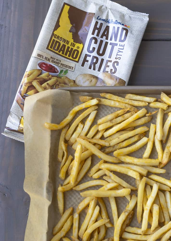 Fries on a sheet pan lined with parchment paper and bag of hand cut fries on the bottom.