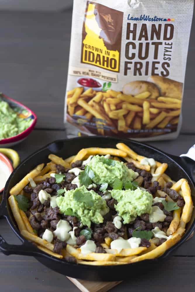 Completed carne asada fries in a skillet with bag of fries in the background.