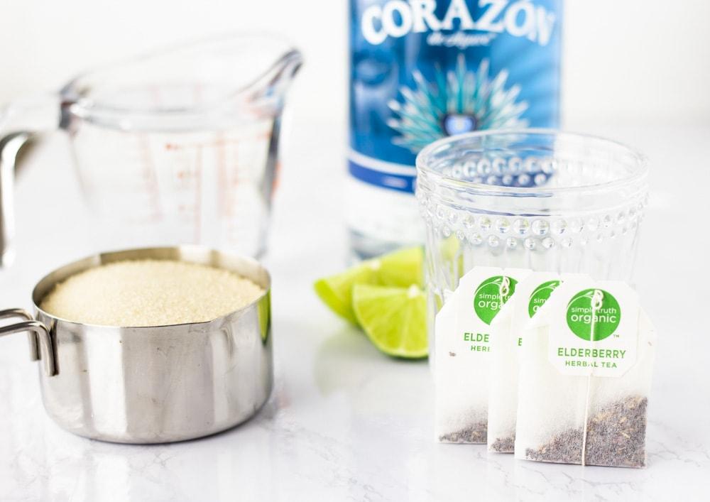Ingredients, cup of sugar, cup of water, 3 bags elderberry tea, limes, and tequila