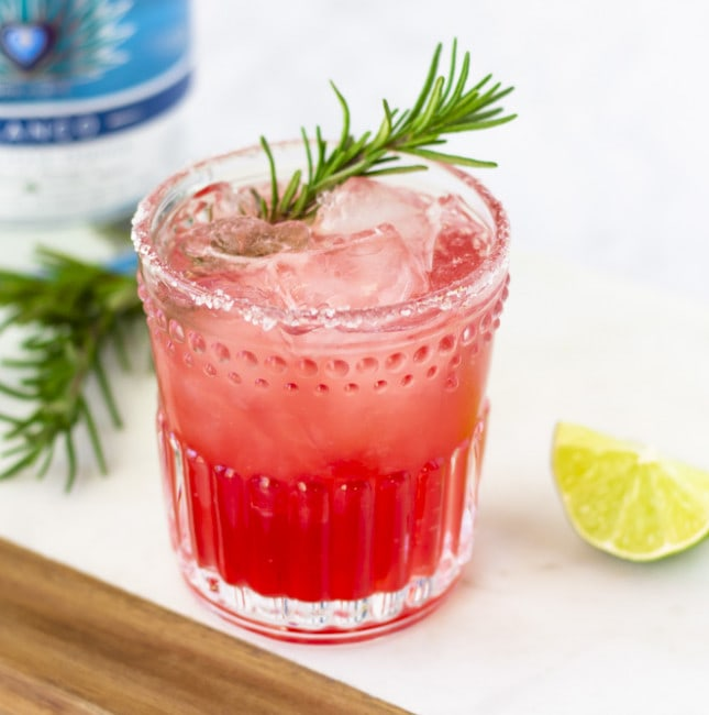 Horizontal view of margarita in a clear glass with a garnish of rosemary.