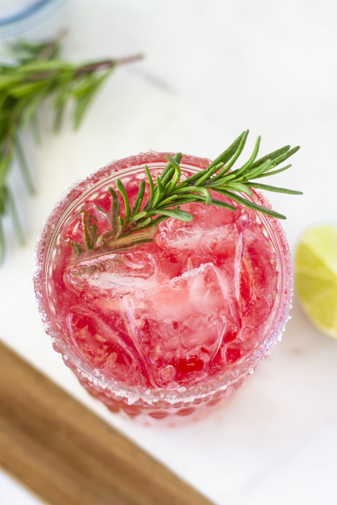 Overhead view of elderberry margarita with a sprig of rosemary in the drink.
