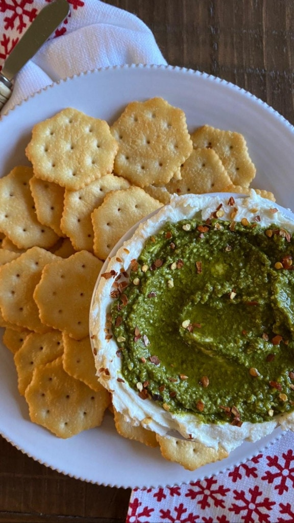 Plate with round crackers and 3 cheese pesto dip on the side.