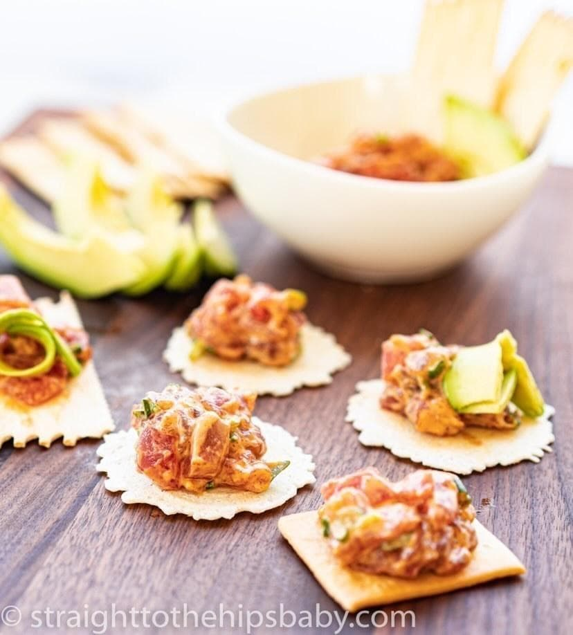 Crackers on a board topped with tuna tartare and slices of avocado in the background.