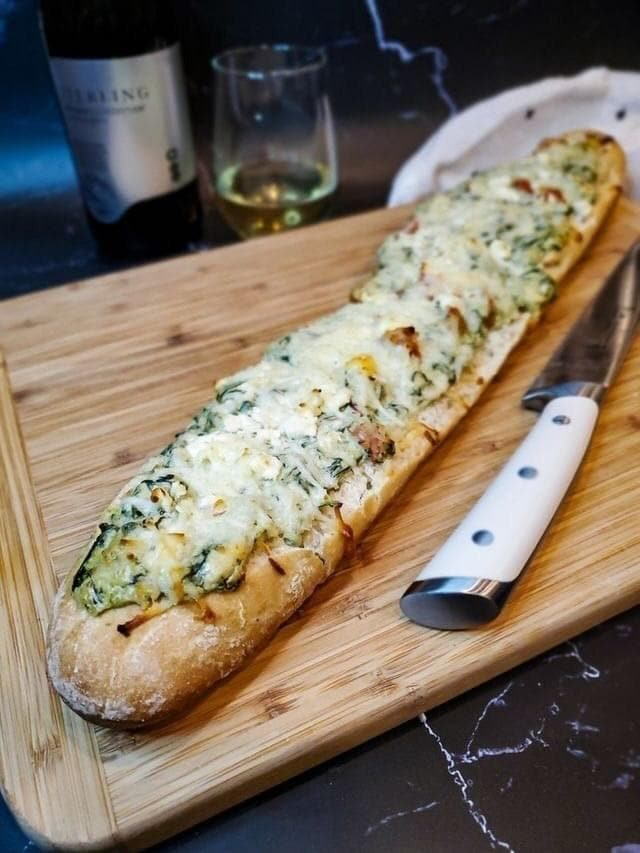 Bread on a cutting board with a white knife on the side and glass of wine in the background.