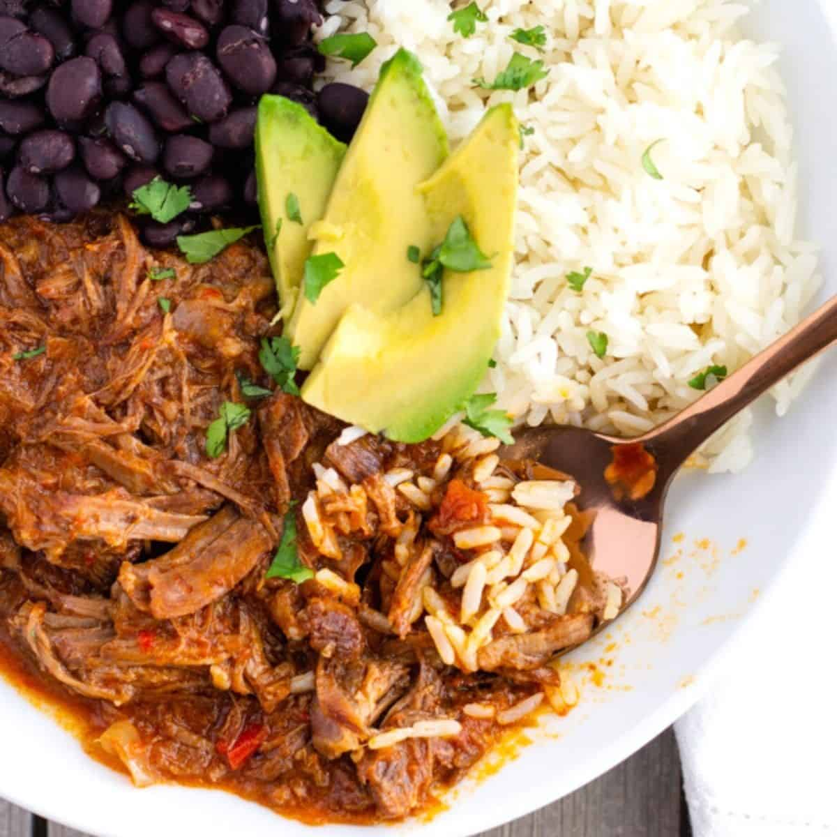 Red shredded beef, white rice, black beans, and sliced avocado on top.