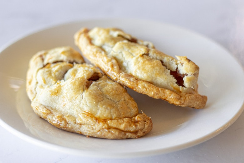 Two baked apple empanadas on a white plate.