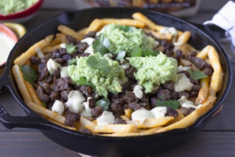 Skillet holding fries topped with steak, queso, and dollops of smashed avocado.