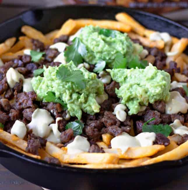 Fries in a cast iron skillet topped with steak, queso, and guacamole.