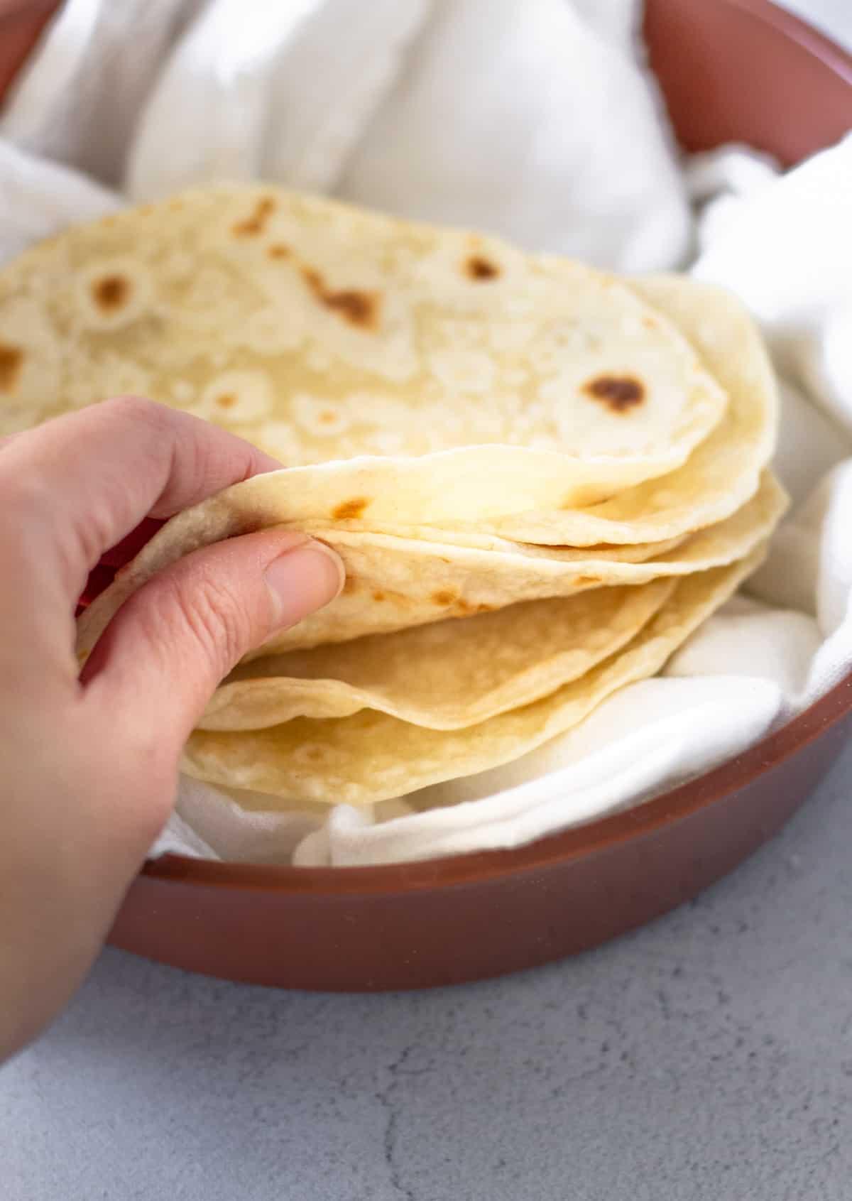 Hand holding tortillas inside the warmer.