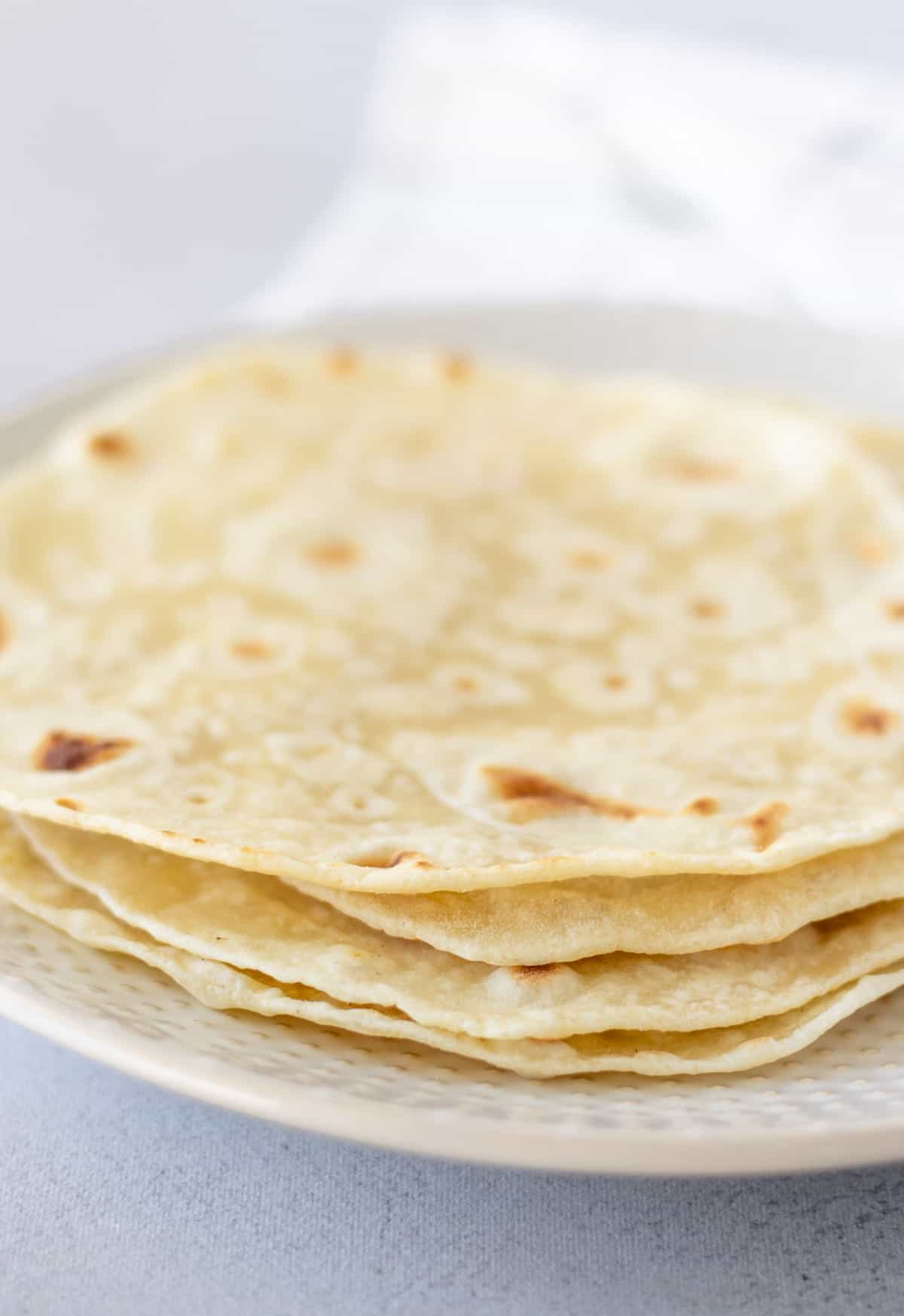 Stack of tortillas on a white plate